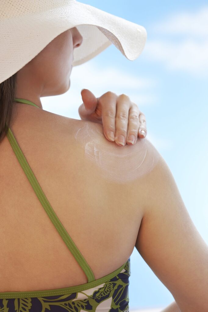 woman applying sunscreen that may be damaging her skin
