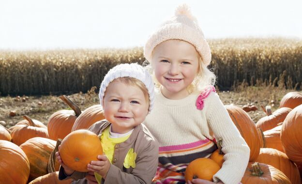girls sitting in field of pumpkins protecting skin from sun